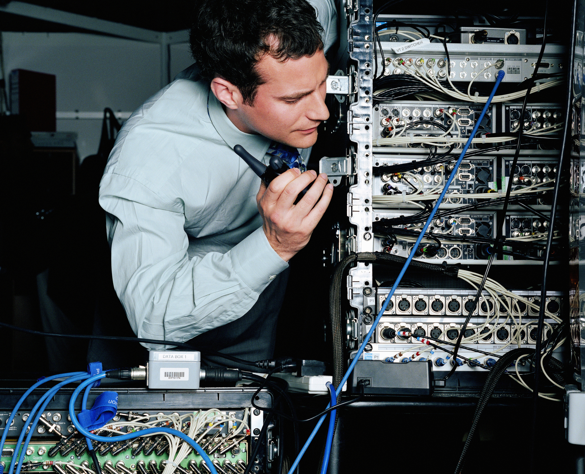 Young businessman using walkie-talkie whilst looking at servers